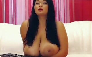 Plump brunette Tammila rubs her tits with oil